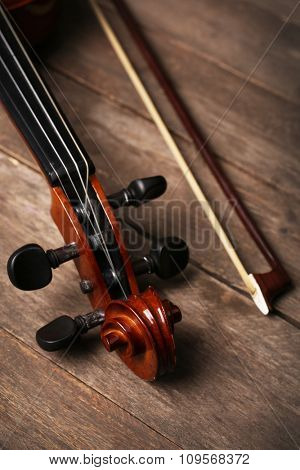 Violin neck on wooden background