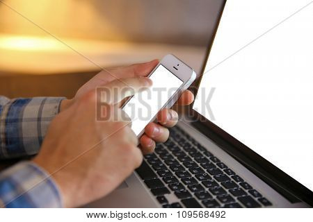 Young man using his phone and laptop, close up