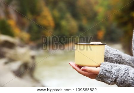 Hand holding coffee cup on nature background