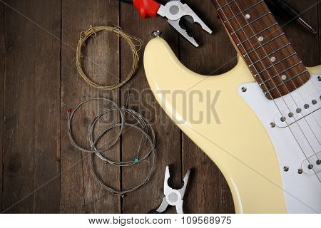 Electric guitar with pliers and cords on wooden background