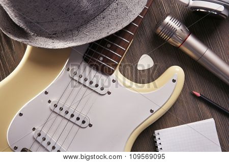 Electric guitar with headphones, hat and microphone on wooden background, close up