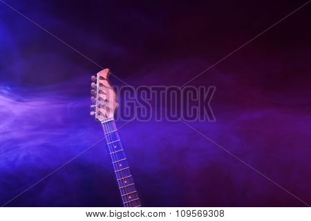Close up view on electric guitars neck in dense smoke under purple light