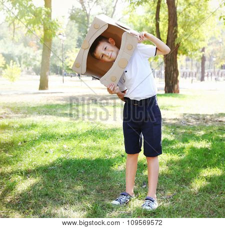Funny boy in carton helmet plays in  the park
