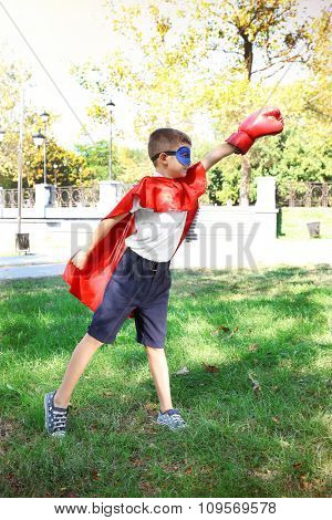 Boy dressed as superhero with boxing gloves plays at the park