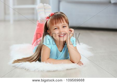 Little cute girl lying on carpet, on home interior background