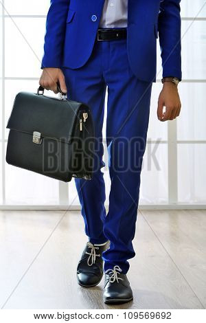 Business man with briefcase on bright background