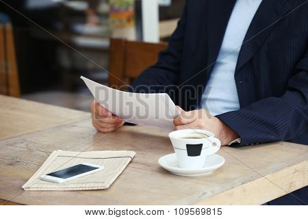 Businessman having lunch and working in a cafe, close-up