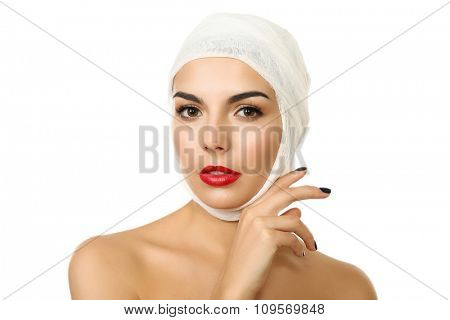 Young beautiful woman with a gauze bandage on her head, isolated on white