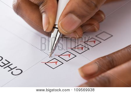 Person's Hand Marking On Checklist Form With Red Pen