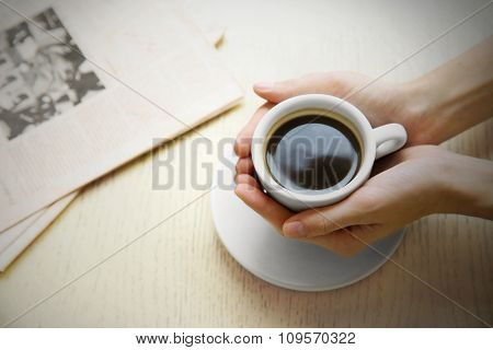 Cup of coffee with hands and newspaper on table background