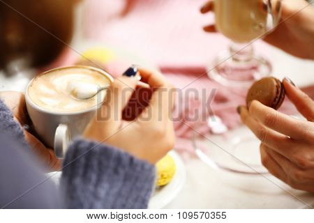 Woman holding cup of coffee in cafe