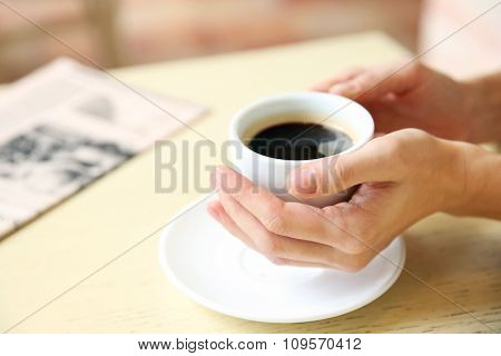 Cup of coffee with hands and newspaper on table in cafe background