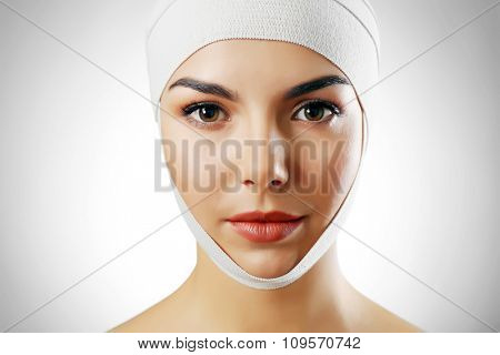 Young beautiful woman with an elastic bandage on her head, on grey background, close-up