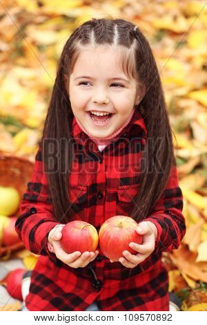 Beautiful little girl holding apples, outdoor