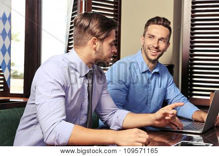 Young men talking in cafe