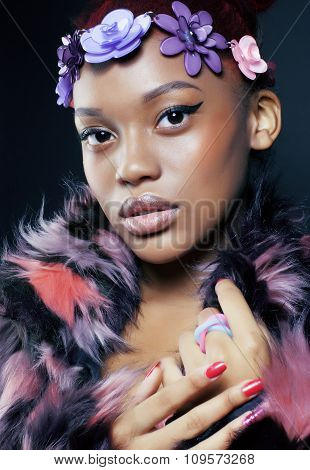 young pretty african american woman in spotted fur coat and flowers jewelry on head smiling sweet et