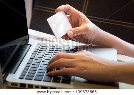 Women's Hand Holding Blank Credit Card Over Laptop : Online Shopping Concept