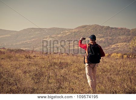 Male Tourist With Backpack Taking Pictures Of  Scenery To Your Smartphone.