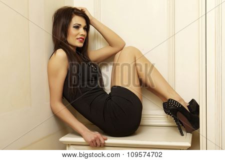 Portrait of a beautiful sexy and attractive young adult brunette sensuality pretty woman posing in black dress in vintage retro style apartment