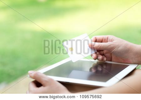 Woman's Hands Holding A Credit Card And Using Tablet Pc. Online Shopping Concept