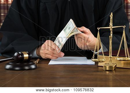 Corrupt Judge Holding Dollar Bundle At Desk
