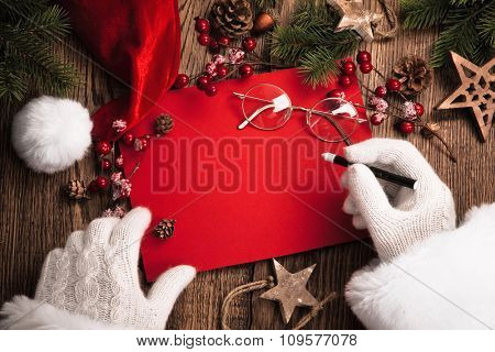Santa Claus with gifts and red card on wooden table