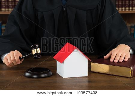 Judge With House Model Hitting Gavel At Desk