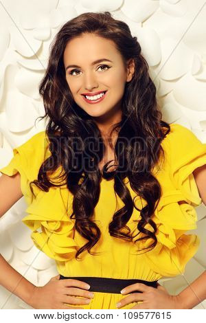 Gorgeous fashion model in bright yellow dress over background of white paper flowers. Beauty, fashion.