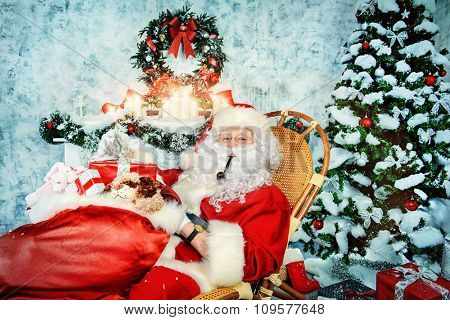 Jolly Santa Claus smoking a pipe and holding a sack with gifts. Christmas interior decoration.