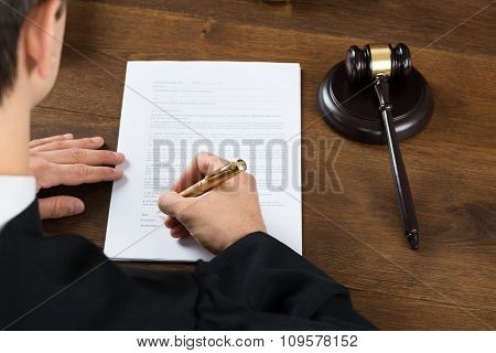 Judge Writing On Legal Documents In Courtroom