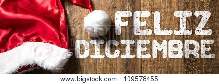 Welcome December (in Spanish) written on wooden with Santa Hat