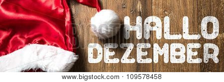Hello December (in German) written on wooden with Santa Hat