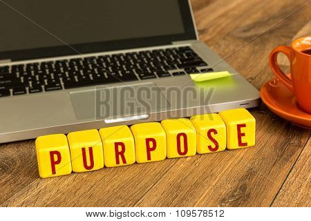 Purpose written on a wooden cube in a office desk