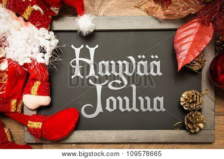 Blackboard with the text: Merry Christmas (in Finnish)