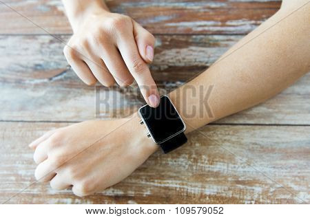business, technology and people concept - close up of woman hands setting smart watch at home
