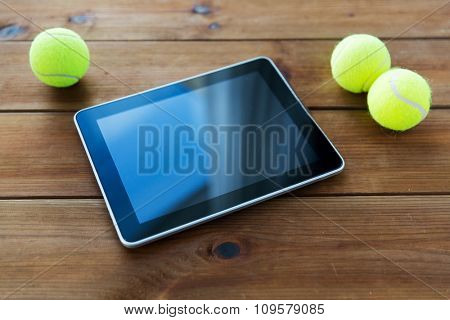 sport, technology, game and objects concept - close up of three yellow tennis balls and tablet pc computer on wooden floor