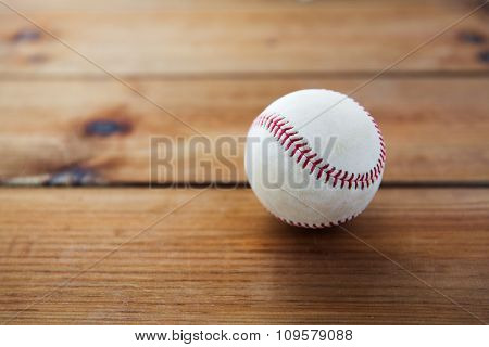 sport, fitness, game and objects concept - close up of baseball ball on wooden floor
