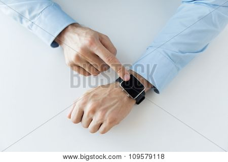 business, technology and people concept - close up of male hands setting smart watch at home