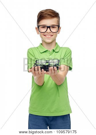 childhood, vision, eyesight, health care and people concept - happy smiling boy in green polo t-shirt with eyeglasses