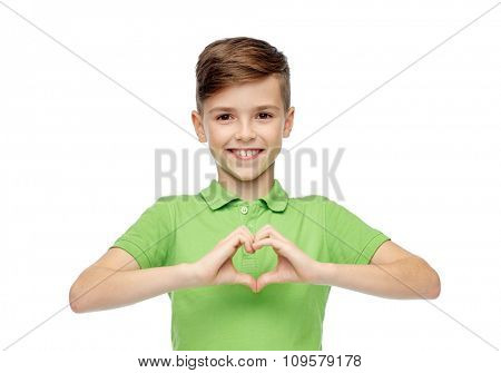 childhood, love, charity, health care and people concept - happy smiling boy in green polo t-shirt showing heart hand sign