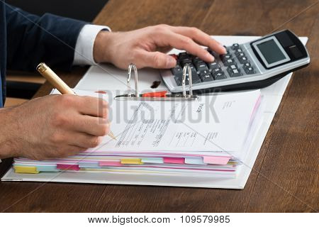 Businessman Using Calculator While Checking Invoice At Desk