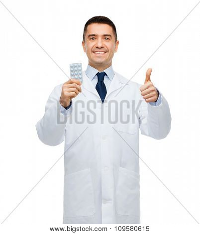 healthcare, profession, people, gesture and medicine concept - smiling male doctor in white coat with tablets showing thumbs up
