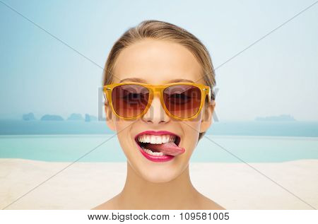 people, expression, vacation, travel and fashion concept - smiling young woman in sunglasses with pink lipstick on lips showing tongue over infinity edge pool background