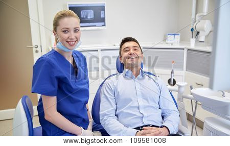 people, medicine, stomatology and health care concept - happy female dentist with man patient at dental clinic office