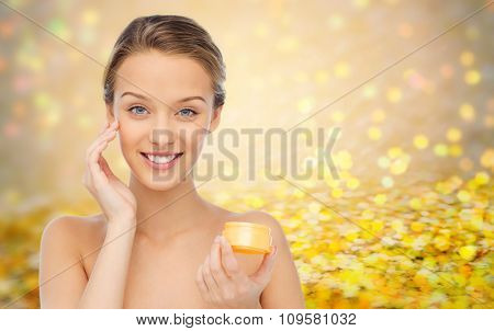 beauty, people, cosmetics, skincare and cosmetics concept - happy young woman applying cream to her face over golden glitter or holidays lights background