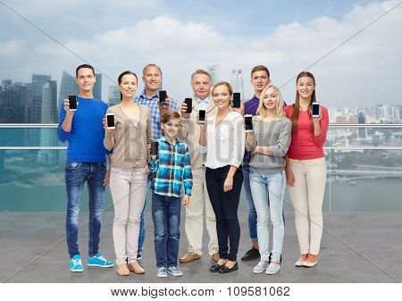 family, technology, generation and people concept - group of smiling men, women and boy with smartphones over singapore city waterside background