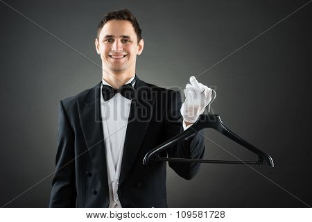 Portrait Of Happy Housekeeper Holding Hanger
