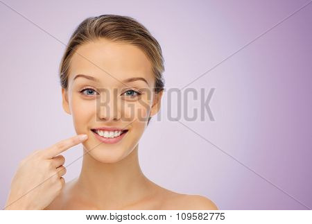 beauty, people, dental care and hygiene concept - happy young woman pointing finger to her smile or teeth over violet background