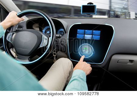 transport, road trip, car driving, technology and people concept - close up of man driving car and pushing start engine button on board computer