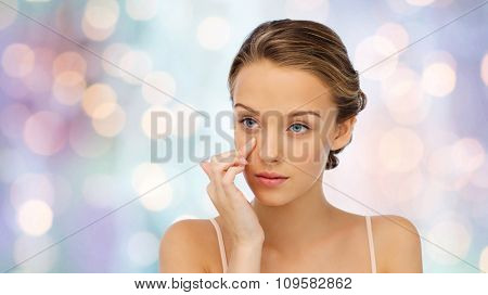 beauty, people, cosmetics, skincare and health concept - young woman applying cream to her face over purple holidays lights background